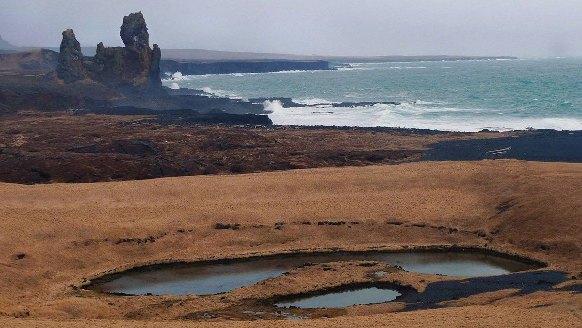 """A group of dramatic sea stacks, referring to locally as the """"Troll Church,"""" overlooks a stretch of Icelandic coastline."""