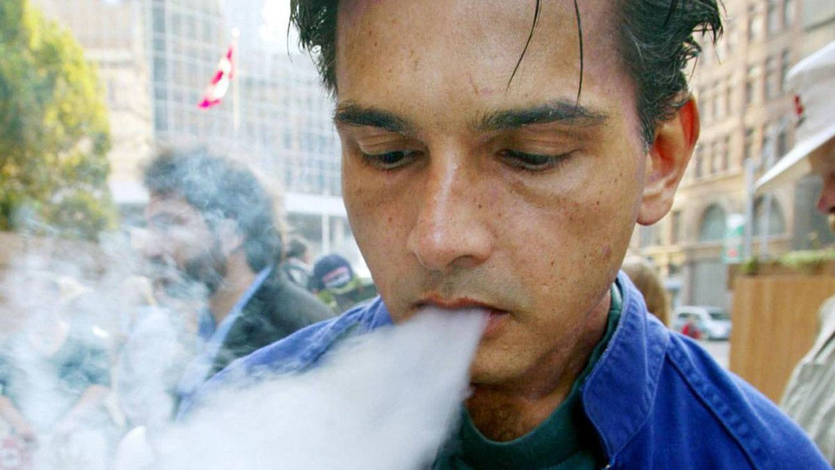 Medicinal marijuana user Julian Roy, who suffers from chronic arthritis, smokes marijuana from a pipe at a protest at Old City Hall in Toronto on September 30, 2002.