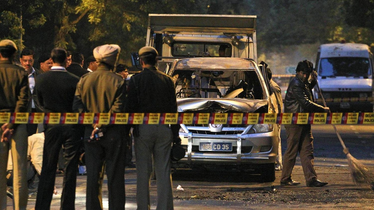 A worker sweeps debris as Indian police officers gather around car belonging to the Israel Embassy, that was damaged in an explosion in New Delhi, India, Monday, Feb. 13, 2012.
