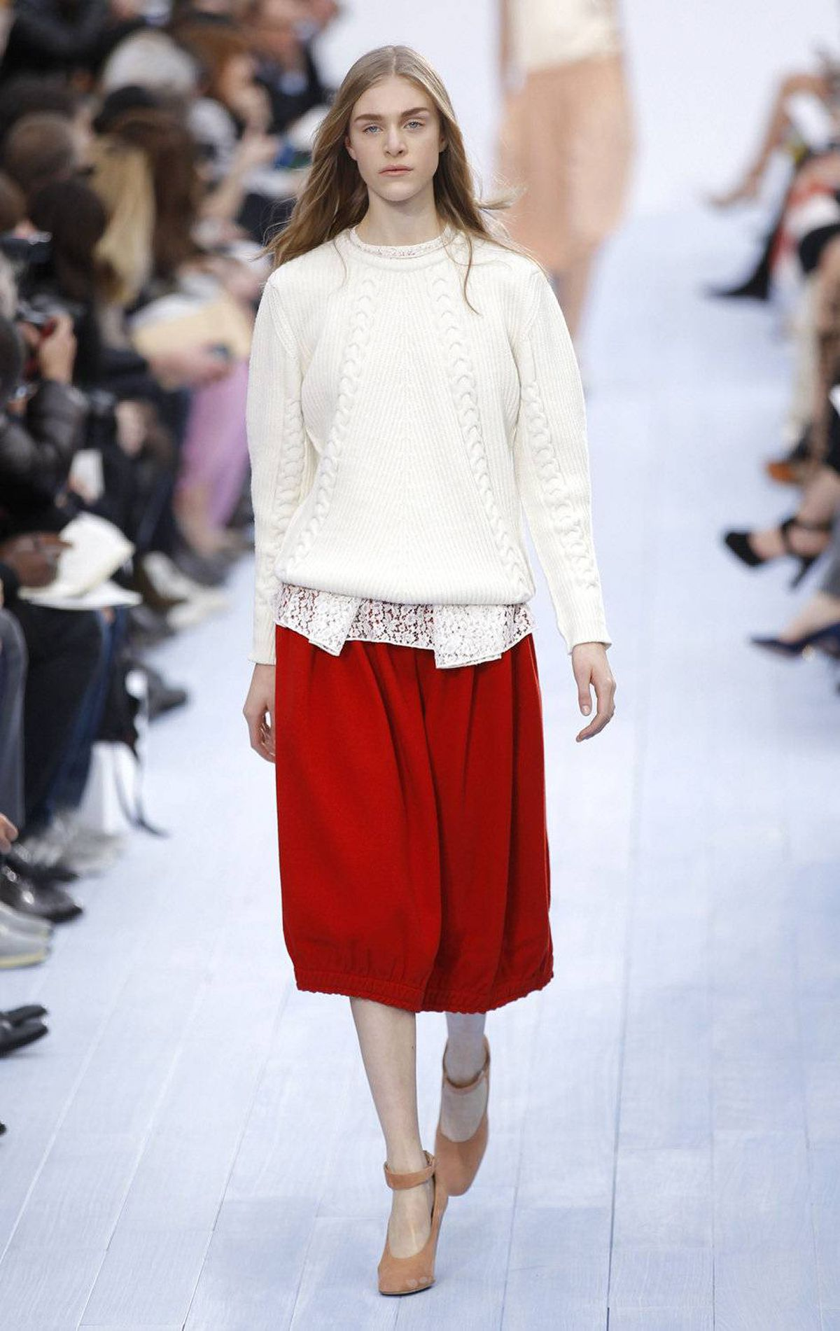 Styling can make all the difference between originality and been-there-designed-that. Here, the folded lace tails poking out of this sweater, with its judiciously applied cable tracks, is understated perfection. Add the crimson red skirt and hello easy dressing, 2012.