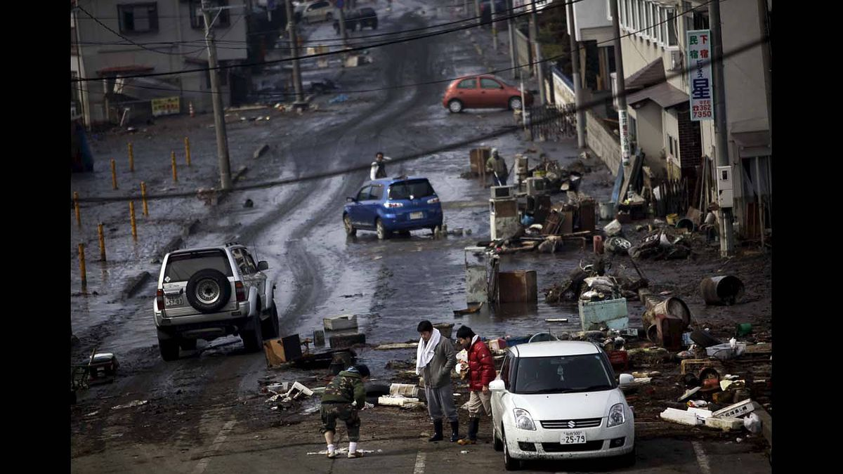 Local people are out on a street to inspect the aftermath of a massive tsunami triggered by March 11 earthquake, in Tagajo, near Sendai, northern Japan, Sunday, March 13, 2011.