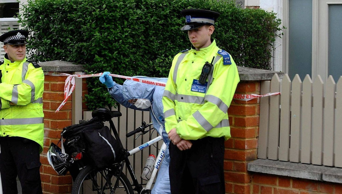 A Police forensics officer leaves a house in Wandsworth, south London, on Thursday May 10, 2012, after two babies were found dead late Wednesday night.
