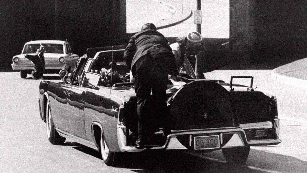 President John F. Kennedy slumps down in the back seat of the presidential limousine after being fatally shot in Dallas on Nov. 22, 1963. Mrs. Jacqueline Kennedy leans over the president while a Secret Service agent stands on the bumper.