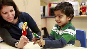 Prathmesh Mistry uses finger puppets to discuss his impressions of kindergarten with researcher and OISE graduate student Kadria Simons during his Junior Kindergarten class at Homestead Public School in Brampton. Photo: Anne-Marie Jackson/ The Globe and Mail