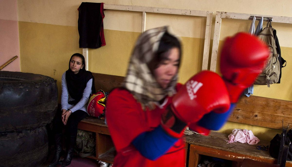 A visitor (L) watches as an Afghan woman practises inside a boxing club in Kabul December 28, 2011. Many in this conservative society still consider fighting taboo for women, and the country's first team of female boxers deal with serious threats.