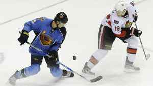 Atlanta Thrashers defenseman Ron Hainsey, left, and Ottawa Senators center Jason Spezza (19) vie for the puck during the third period of an NHL hockey game, Sunday, March 27, 2011, in Atlanta. Atlanta won 5-4 in a shootout. (AP Photo/John Amis)