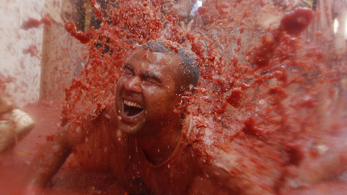 """A reveller is covered with tomato pulp after the annual """"Tomatina"""" (tomato fight) in the Mediterranean village of Bunol, near Valencia August 31, 2011."""