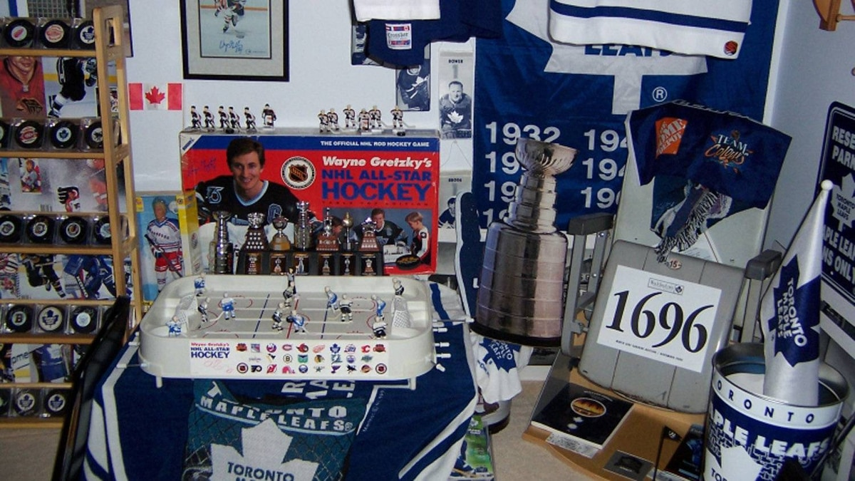 A Wayne Gretzky original tabletop hockey game. Above it is a personally autographed Gretzky photo, and beside it, a stadium seat from Maple Leaf Gardens, with the auction number he used to purchase it, sitting on top