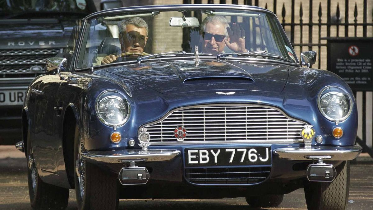 Britain's Prince Charles, right, waves as he leaves his official residence, Clarence House in London, in his vintage Aston Martin with an unidentified driver on Saturday. It's the same car William and Kate drove away from Buckingham Palace in the night before.