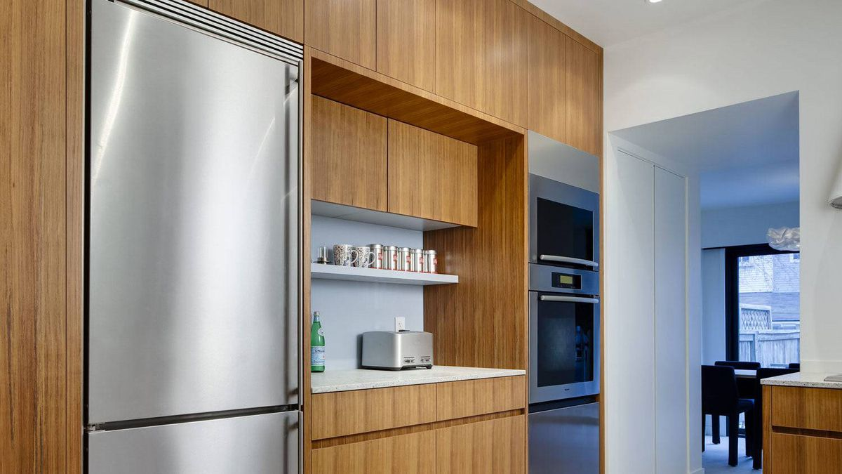 To balance the height of the stainless steel fridge, a bottom drawer under the stainless steel Miele oven was also faced in stainless steel. A top-hinged panel conceals the microwave and crowning it all is another small piece of stainless steel.