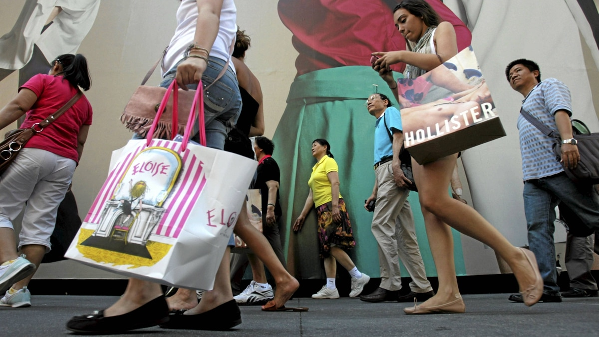 Pedestrians carrying shopping bags make their way along Fifth Avenue in New York.