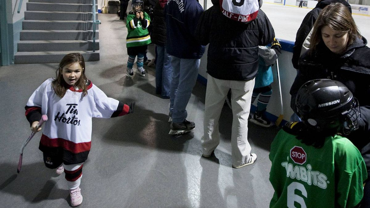 Parents put the final touches to their daughters' hockey equipment for a game of shinny during the intermission of a CWHL game between the Toronto Aeros and Burlington Barracudas in Burlington, Ont. Saturday, November 6, 2010.