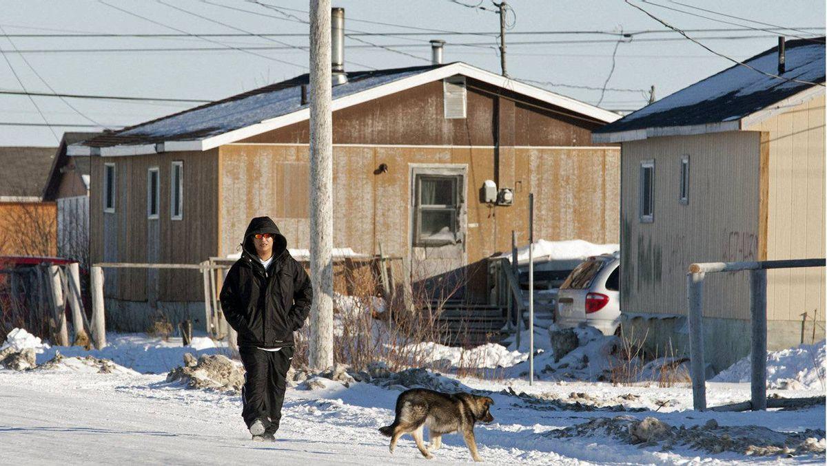 A man walks down the street in Attawapiskat, Ont., on Nov. 29, 2011.