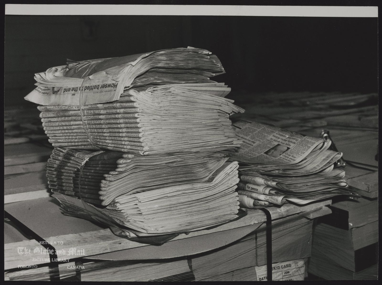 NEWSPAPERS [Piles of Globe and Mail newspapers bound and ready to be delivered].