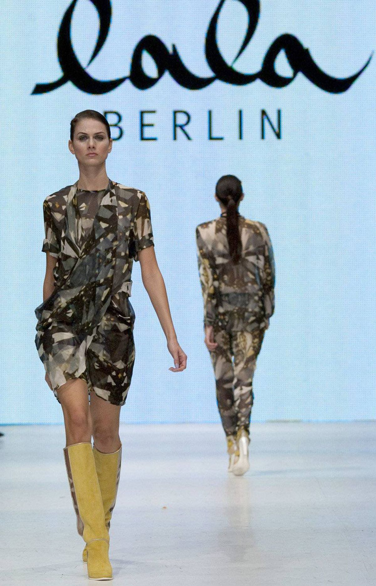 Berlin's focus veered from classically feminine looks to sharp lines and a darker palette of army greens, sheer browns and muted camouflage print. As the show - and the first night of Fashion Week - drew to a close, saturation was slowly stripped altogether and the models left the runway in black on black.