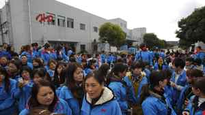 Workers on strike block the entrance gate of the Hi-P International factory in suburban Shanghai. The facility makes electronics products for Apple and BlackBerry maker Research In Motion.