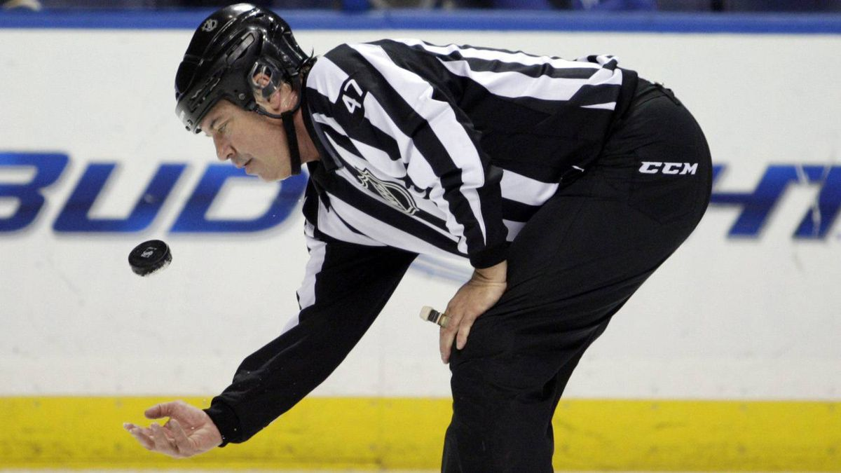 NHL linesman Dan Schachte (47) tosses the puck before a face-off in the first period of an NHL hockey game between the St. Louis Blues and the Minnesota Wild, Saturday, Feb. 18, 2012 in St. Louis. Schachte is officiating in his 2000th NHL game.(AP Photo/Tom Gannam)
