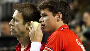 Canada's Daniel Nestor (L) and Milos Raonic talk while their doubles team plays against France during the Davis Cup tennis match in Vancouver, British Columbia February 11, 2012. REUTERS/Ben Nelms
