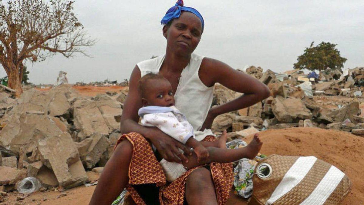 A pregnant Angolan mother is seen with one of her five children on the southern edge of Luanda in August, 2009.