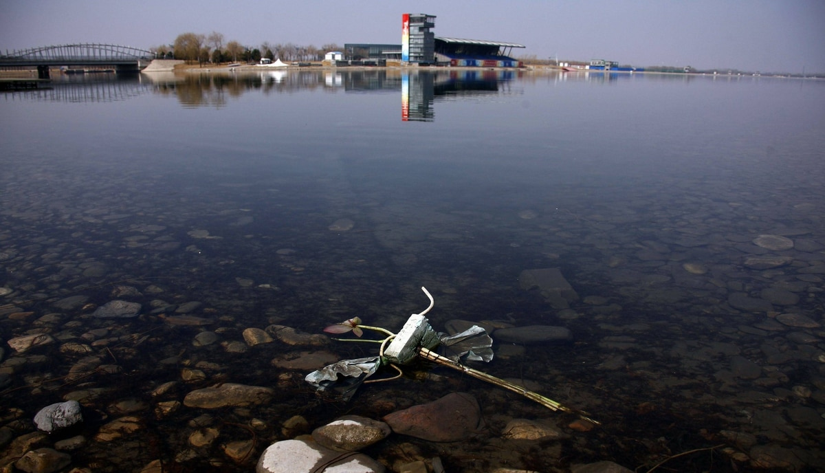 A flower-shaped lamp can be seen discarded into the lake of the deserted former venue for the 2008 Beijing Olympic Games rowing competition, located on the outskirts of Beijing March 27, 2012.