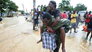 A man helps a woman to cross a flooded road for money in Leogane, 33 km south of Port-au-Prince, on November 6, 2010.