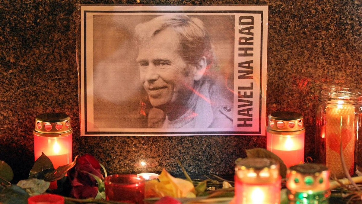 "A portrait of former Czech President Vaclav Havel, with a text that reads: ""Havel To The Castle,"" a popular slogan during the Velvet Revolution of 1989, lies among candles left by mourners at the base of a statue of St. Wenceslas to commemorate Havel's death on December 18, 2011 in Prague, Czech Republic."
