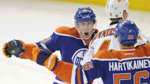 Edmonton Oilers' Ryan Nugent-Hopkins, left, celebrates his goal on the Calgary Flames with teammate Teemu Hartikainen, right, during first period NHL hockey game action in Edmonton on Friday, March 16, 2012.