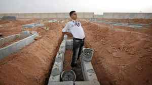 Boy Scout, Mohammed El-Bagrmi, 16, stretches his back before returning to the construction of graves at Benghazi's largest grave site.