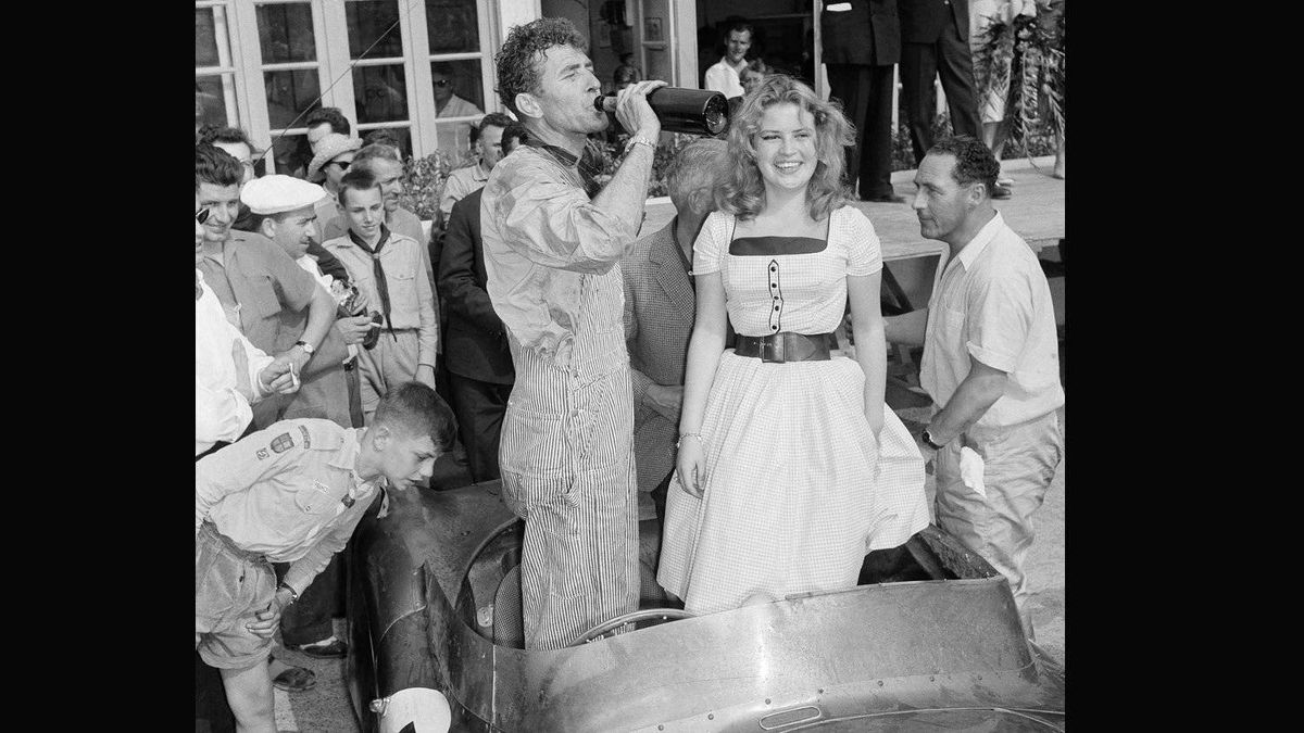 Shelby enjoys a swig of champagne after combining with British veteran Roy Salvadori to win the 24-Hour Endurance Auto Classic at Le Mans, France in 1959. Dressing up the picture is Miss Sophie Destrade, of France. She was Miss Europe of 1959.