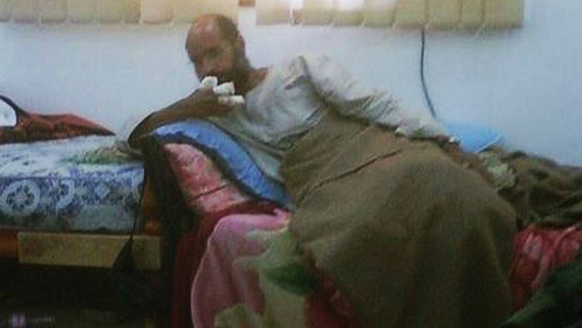 Saif al-Islam, son of the late former Libyan leader Muammar Gaddafi, sits after his capture, with his fingers wrapped in bandages and his legs covered with a blanket, at an undisclosed location, in this photograph aired on Free Libya TV on November 19, 2011. The International Criminal Court Prosecutor's Office said on Saturday it had received confirmation of the arrest of Gaddafi's son, Saif al-Islam, from Libya's Ministry of Justice.