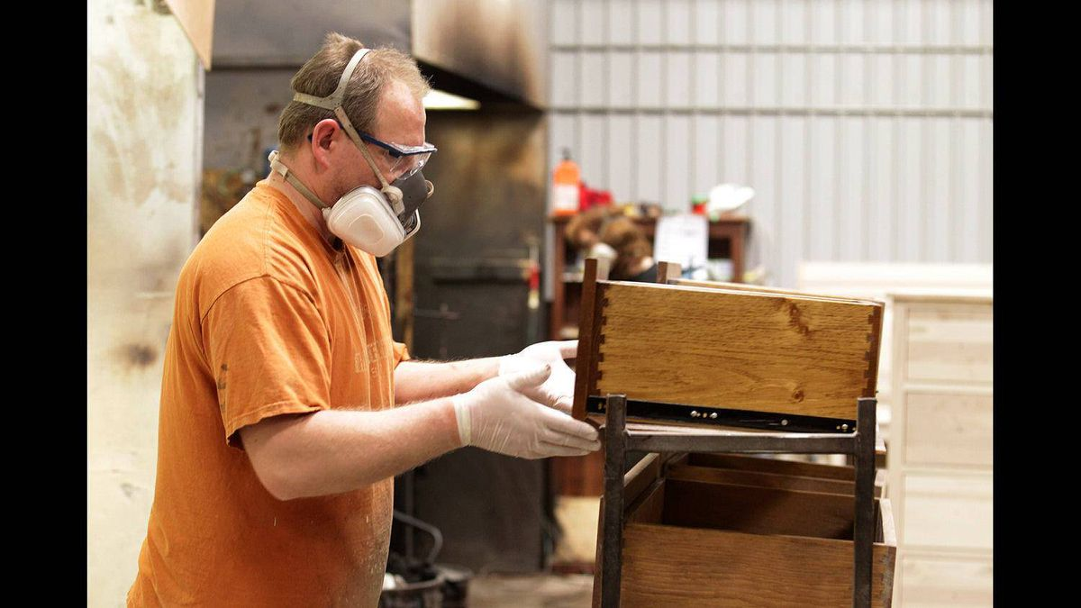 A Vokes Furniture employee works in the lacquer spraying area at the company's factory in Shallow Lake, Ont.