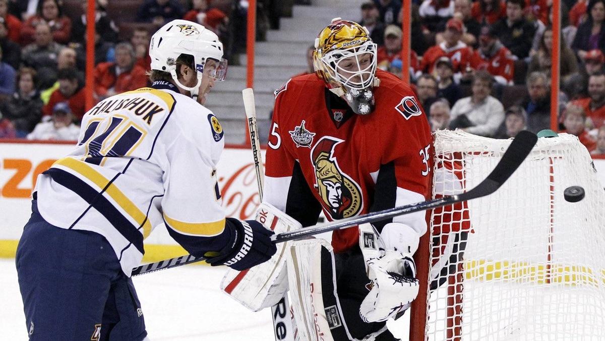 Nashville Predators' Matt Halischuk knocks the puck down behind Ottawa Senators' goalie Alex Auld during the first period of their NHL hockey game in Ottawa February 9, 2012.