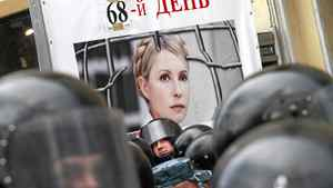 """Riot police stand guard near a board, displaying a portrait of Ukrainian former prime minister Yulia Tymoshenko and reading """"The 68th day"""", during a rally near the Pecherskiy district court in Kiev October 11, 2011."""