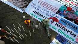 A demonstrator lights candles next to a banner with a picture of anti-mine activist Mariano Abarca Robledo during a protest outside the Canadian embassy in Mexico City, on Dec. 3, 2009.