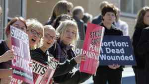 Demonstrators hold up pro-choice signs, left, as an opposing group holds up anti-abortion signs, during a rally to protest South Dakota's new anti-abortion law outside the Federal Court building in downtown Sioux Falls, S.D., March 9, 2006.