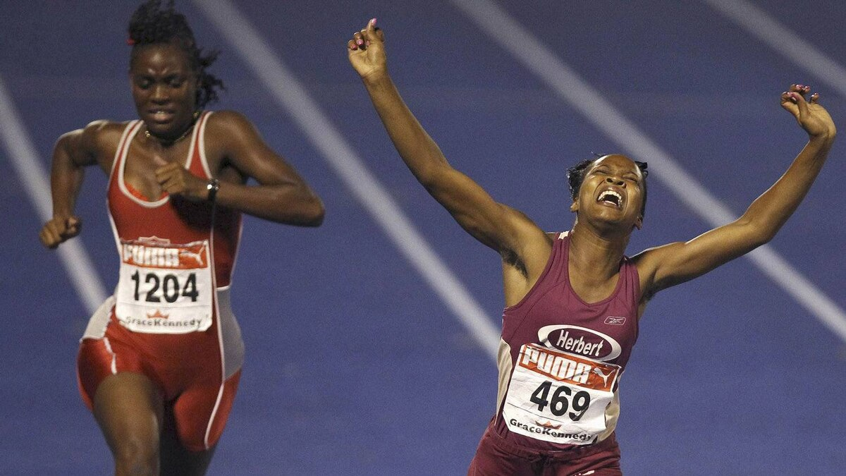Girls 100 meter dash CLASS 1, for competitors between the ages of 17 - 19, winner Seidatha Palmer (R) celebrates her first place finisher during Jamaica's Inter-Secondary Schools Boys and Girls Athletics Championships, also known as Champs, at Kingston city March 30, 2012. REUTERS/Ivan Alvarado