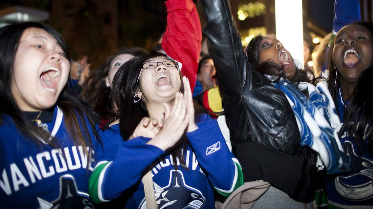 Fans celebrate the Vancouver Canucks' Game 5 win against the San Jose Sharks, at CBC plaza in Vancouver.