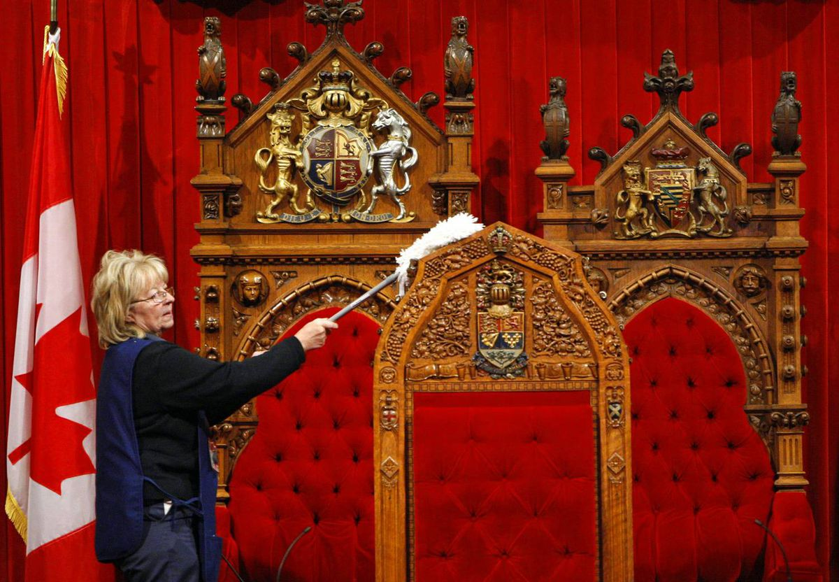A worker cleans the speaker's chair in the Senate chamber in preparation for the return of Parliament on Nov. 17, 2008.