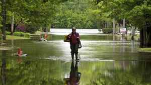 A Quebec man sloshes through the flooded streets of St-Jean on May 27, 2011.