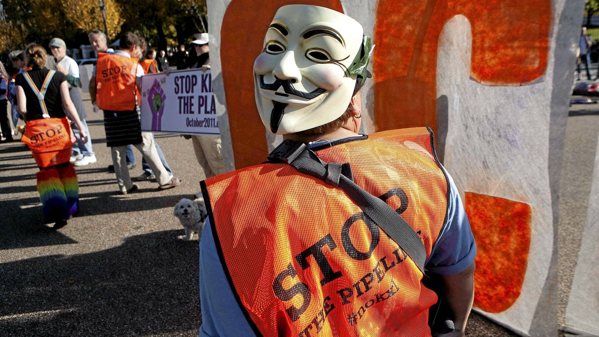 A demonstrator wearing a Guy Fawkes mask on the back of her head, calls for the cancellation of the Keystone XL pipeline during a rally in front of the White House in Washington November 6, 2011.