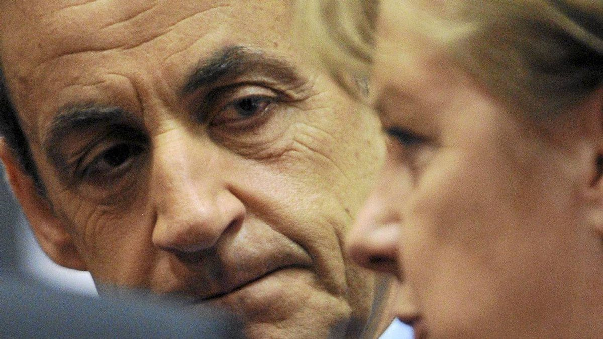 French President Nicolas Sarkozy, left, speaks with German Chancellor Angela Merkel during a round table session at an EU summit in Brussels on Friday, Dec. 9, 2011.