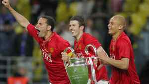 Manchester United's captain Rio Ferdinand (L) and Wes Brown run with the trophy after beating Chelsea in the final of the UEFA Champions League football match at the Luzhniki stadium in Moscow on May 21, 2008. The match remained at a 1-1 draw and Manchester won on penalties after extra time. Getty Images / Alexander Nemenov