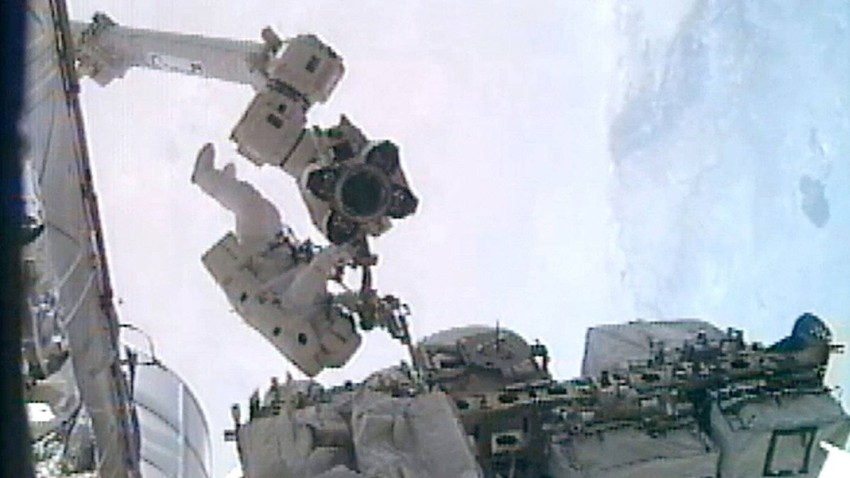 NASA astronaut Ronald Garan (L) installs a foot restraint on the Canada Arm 2 as he and astronaut Michael Fossum do repairs on the International Space Station during a planned six-and-a-half-hour spacewalk July 12, 2011 in space.