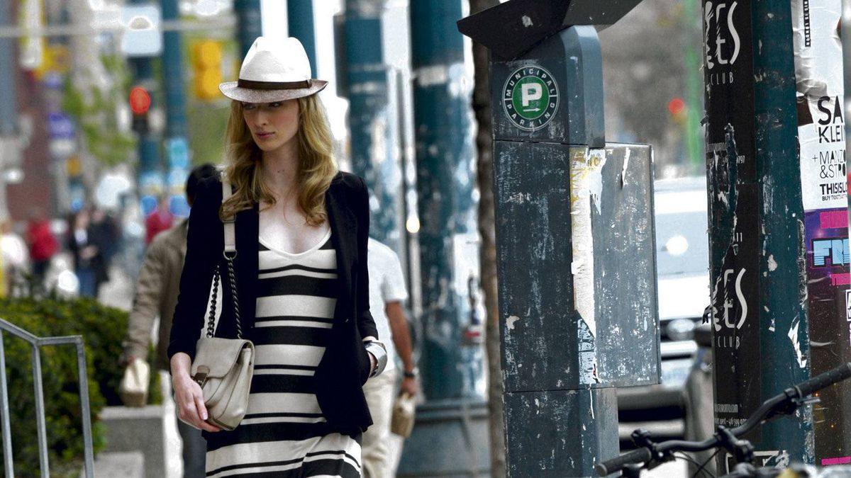 """The """"real-way"""" model struts down the street in her striped maxi dress."""
