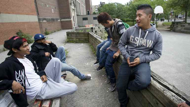 Tenzin Namgyal, 17, (right( uses his cellphone outside Parkdale Collegiate Institute in Toronto on Sept. 6, 2011.