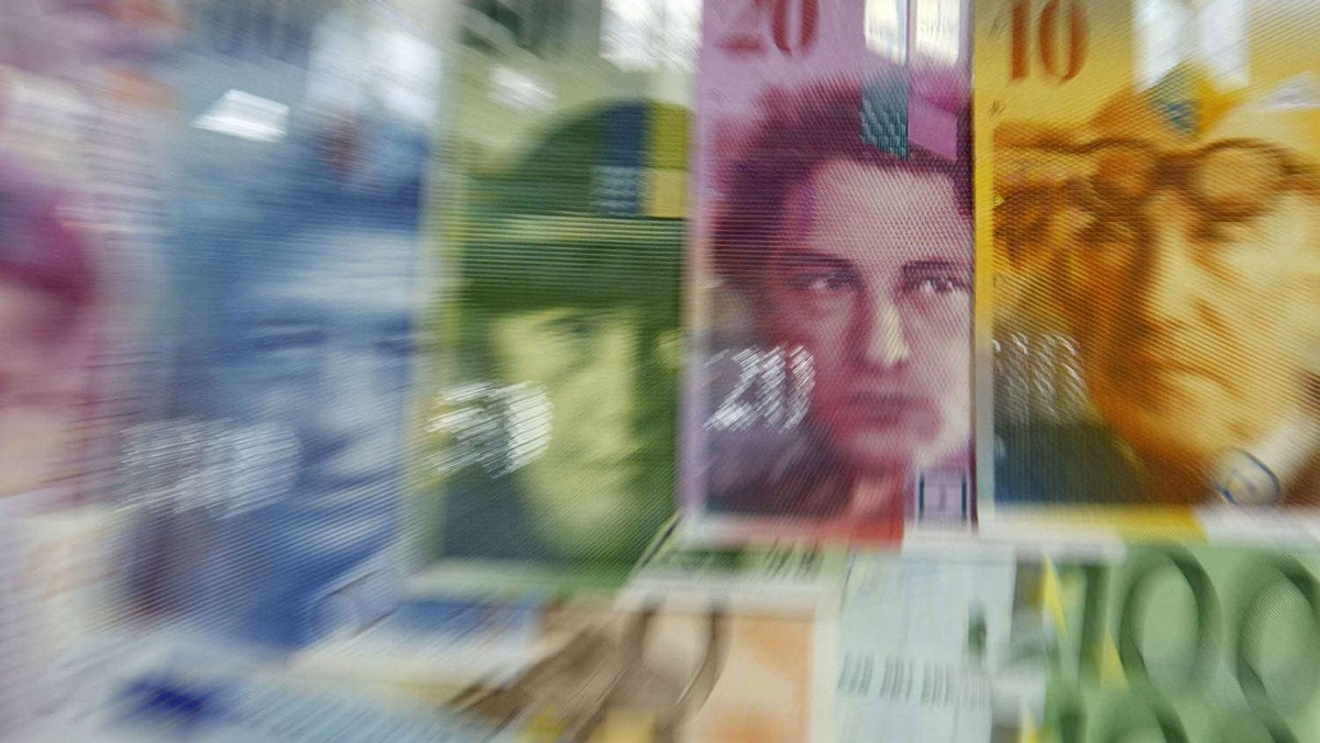 Varoius Euro banknotes lay next to various Swiss Franc notes in this picture illustration at a bank in Warsaw, July 18, 2011.