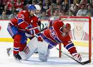 Hal Gill picks up the loose puck to the side of teammate Jaroslav Halak of the Montreal Canadiens in Game Six of the Eastern Conference Quarterfinals against the Washington Capitals during the 2010 NHL Stanley Cup Playoffs at the Bell Centre on April 26, 2010 in Montreal, Quebec, Canada.