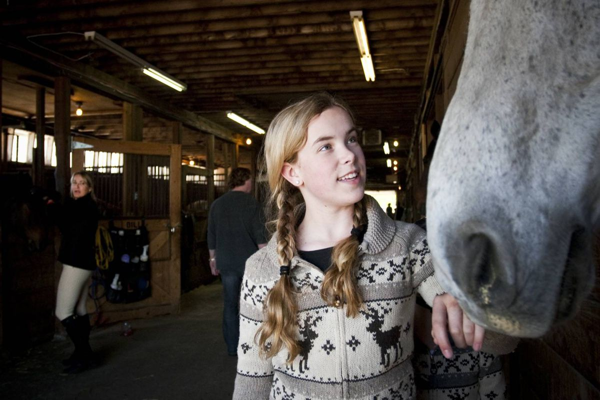 Collen Taylor (L) watching her daughter Hannah Taylor, 13, visiting horses in the stables before their riding lesson.