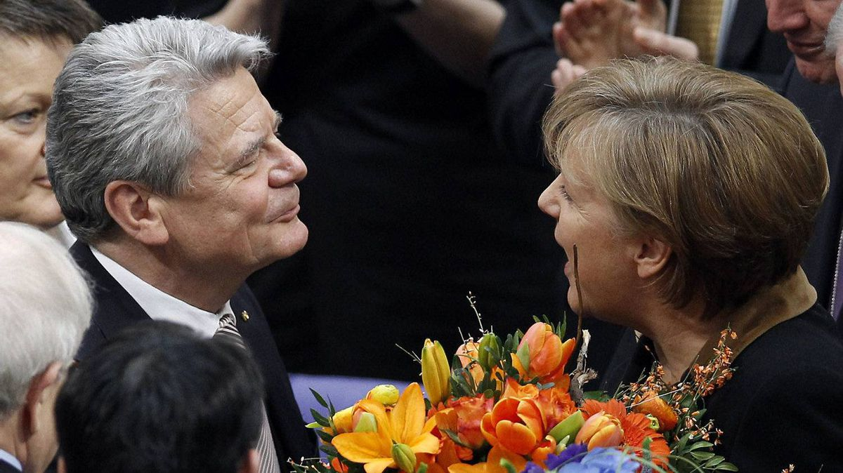 German Chancellor Angela Merkel, right, hands over a bunch of flowers to new elected German President Joachim Gauck, left, at the parliament building Reichstag in Berlin, Germany, Sunday, March 18, 2012.