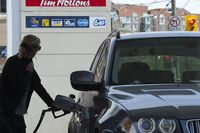 A woman pumps gas in Toronto on Tuesday, May 10, 2011.